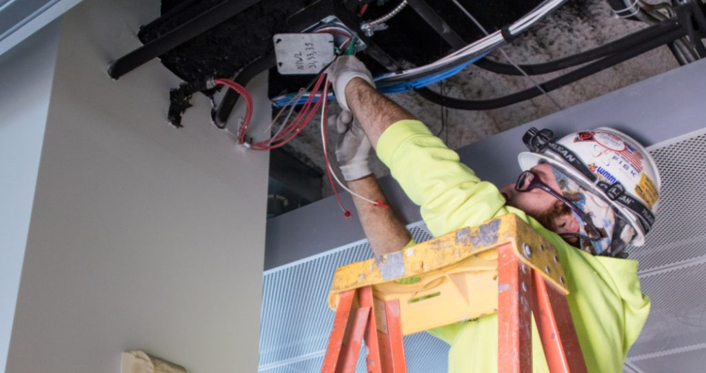 Commercial Electrician working on a junction in ceiling